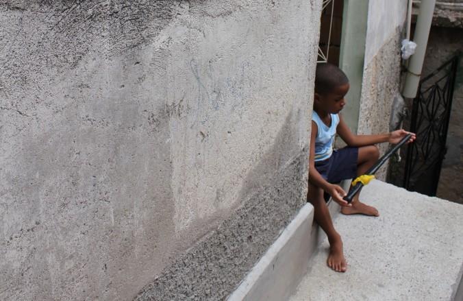 Kind in einer Favela mit Spielzeugwaffen (Foto: Julia Jaroschewski)